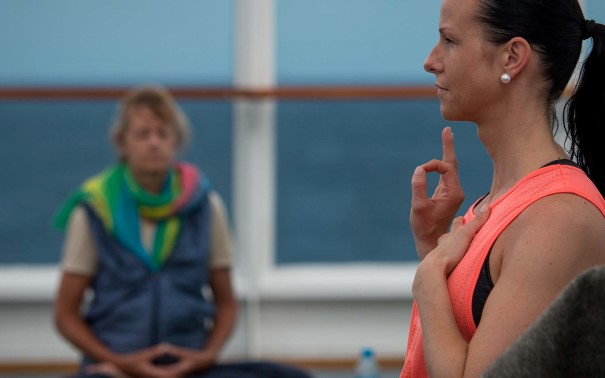 A professional instructor guides guests through a yoga and meditation session out on deck.