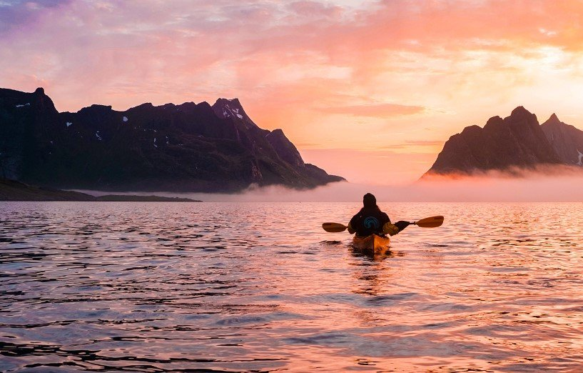Person kayaking in Reine,Lofoten, during sunset.