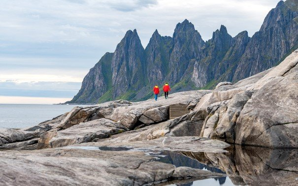 Two people in red jackets hiking on cliffs in front of the mountains on Senja.