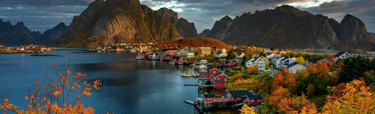 Reine, a small village with wooden houses next to the sea, surrounded by mountains and autumn colored trees.