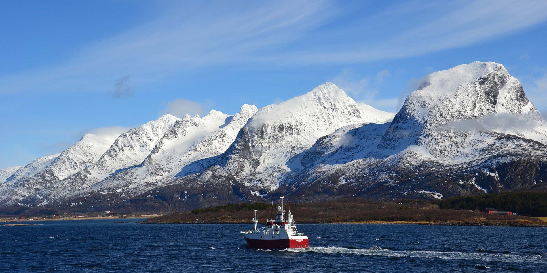 A fishing boat in front of the Seven Sisters mountain chain