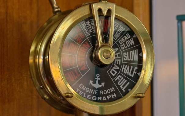 A gold clock sitting on top of a wooden table