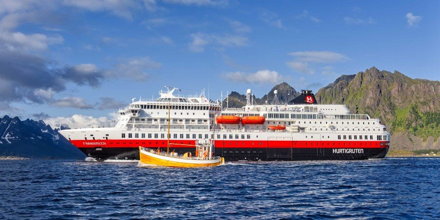A fishing boat next to MS Finnmarken in Lofoten